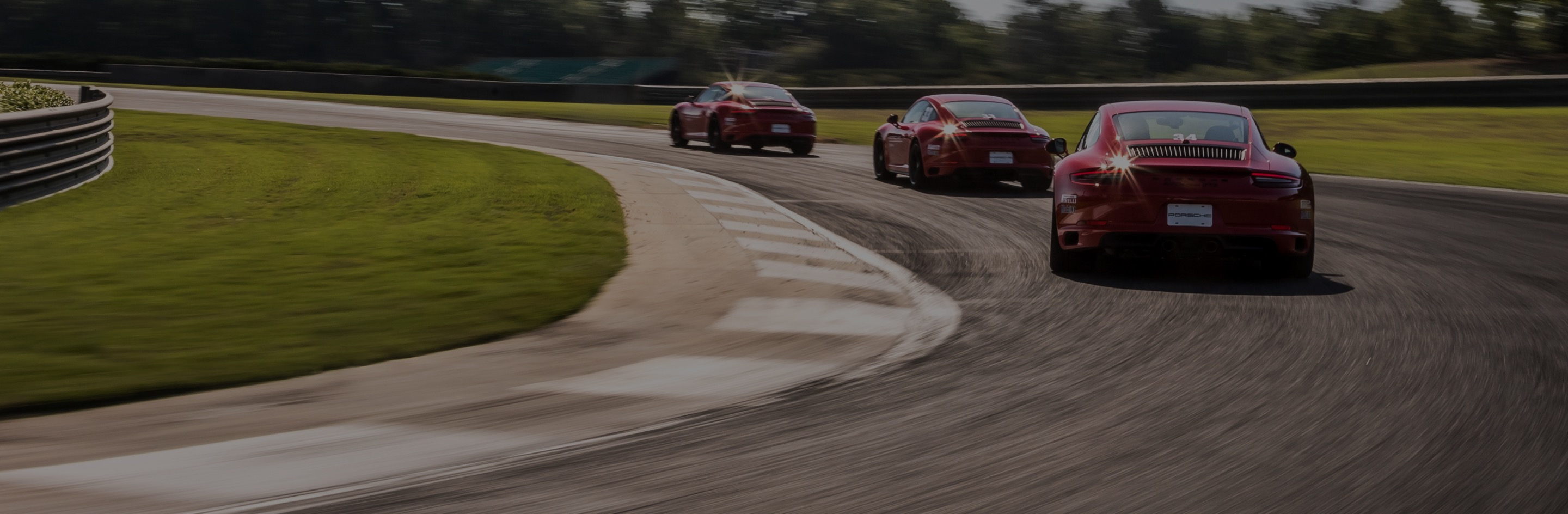 three red porsches rounding a corner on the track
